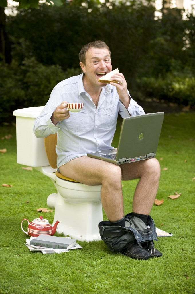 Television personality and former cricketer Phil Tufnell demonstrates some of the activities that British people get up to whilst on the toilet in London's Paddington Street Gardens for the launch of the Gut Week
